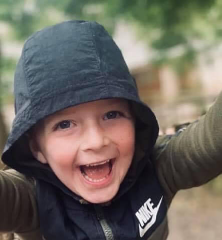 happy-smiling-boy-playing-with-arms-in-the-air-with-hood-up-with-autism-at-bibic